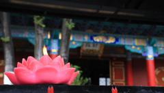 Burning lotus blossom candle against temple Stock Footage