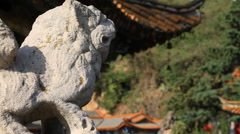 Stone lion standing against Yuantong Temple in Kunming, China Stock Footage