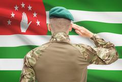 Soldier in hat facing national flag series - Abkhazia - stock photo
