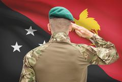 Soldier in hat facing national flag series - Papua New Guinea - stock photo