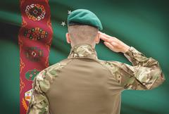 Soldier in hat facing national flag series - Turkmenistan - stock photo