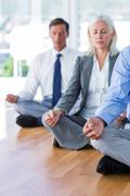 Business people doing yoga on floor Stock Photos