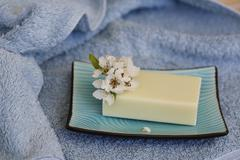 Soap piece with flower in soap dish terry towel - stock photo