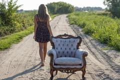 Girl 14 years walking along a track an old armchair in front - stock photo
