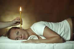 Woman 44 years is being treated with an ear candle Stock Photos