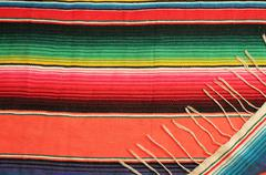 Traditional Mexican fiesta poncho rug in bright colors background with copy - stock photo
