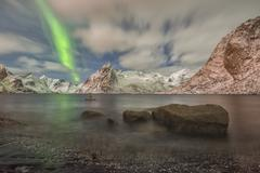 Small aurora with clouds rocks by the ocean mountains at the back Hamnoy Island - stock photo