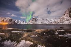 Stock Photo of Small aurora with clouds rocks and ice small town and mountains at the back