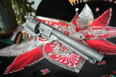 sequin and decorative ornate mexican hat ready for a fiesta with a gun - stock photo