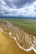 Sandy sea shore on storm - stock photo