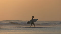 Silhouette Surfer Walks With Golden Sunset Footsteps 4K Stock Footage