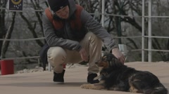 Young man petting a dog on nature. - stock footage