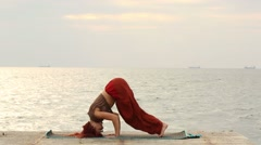 Beautiful girl performs asana against the sea Stock Footage