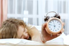 Young woman with alarmclock on the bed. - stock photo
