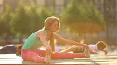 Young red-haired woman practicing yoga in a city park at sunset. - stock footage