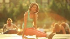 Young red-haired woman practicing yoga in a city park at sunset. Stock Footage