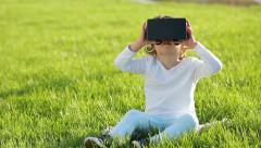 Virtual reality mask. The little girl with surprise uses head-mounted display. Stock Footage