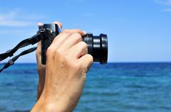 young man taking a picture in front of the sea - stock photo