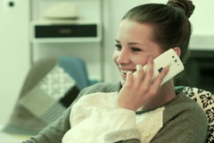 Young woman talking on cellphone sitting on chair at home NTSC Stock Footage