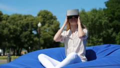 Virtual reality mask. Girl with pleasure uses head-mounted display in city park. Stock Footage