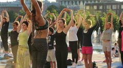A large group of active young people practicing yoga in a city park Stock Footage
