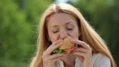 Young slim woman with an appetite for eating a hamburger in a city park. Stock Footage