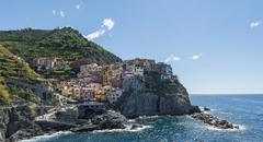 Colorful houses on cliffs Manarola Riomaggiore Cinque Terre La Spezia Liguria - stock photo