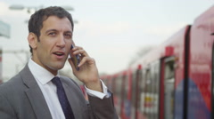 4k handsome businessman talking on his cellphone at train station Stock Footage