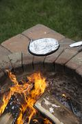 Cooking a pan of popcorn in a foil covered pan over a garden fire pit - stock photo