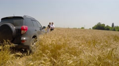 The Chiefs have come by car to watch a field of wheat. - stock footage