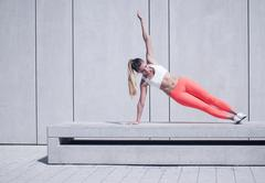 Stock Photo of Sporty Woman Doing Side Plank Exercise on Platform