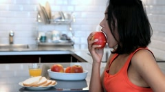 Woman in the kitchen eating red apple Stock Footage