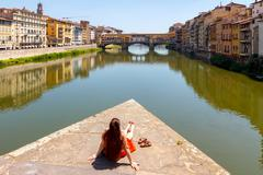 Florence. Woman tourist admires the Ponte Vecchio. Stock Photos