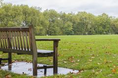 Lonely bench in a rainy day - stock photo