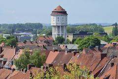 The water tower with its pointy tiled roof rising above the houses in the city - stock photo