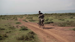 African man cycling on savannah dirt road, Samburu, Kenya, Africa - stock footage