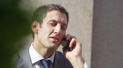 4k Cheerful businessman having phone conversation outside office building - stock footage