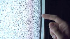 Man Touching TV Screen with Static Noise in Dark Room Stock Footage