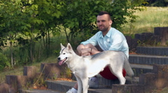 man and his dog in the park, husky dog - stock footage
