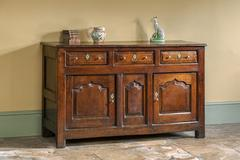 old english antique kitchen dresser base on flagstone floor - stock photo