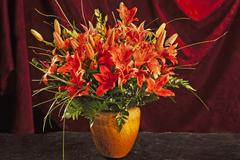 Bouquet of lilies vase in front of a red curtain - stock photo