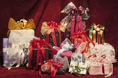 Artfully wrapped gifts on red fabric - stock photo