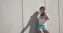 Girl with long hair wearing sunglasses and hat , summer hot day , posing against Stock Footage
