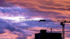 Silhouette Crane Working In Construction Site And Twilight Sky (pan shot) - stock footage