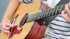 Teen playing guitar, closeup Stock Footage