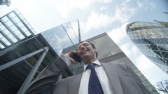 4k, Successful businessman talking on mobile phone in London financial district - stock footage
