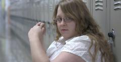 Sad and upset high school student sitting against lockers 4k - stock footage