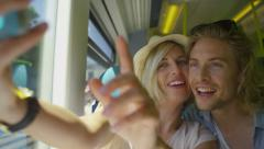 Attractive couple in love take a photo of themselves on a moving train Stock Footage