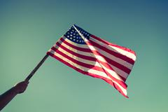 Stock Photo of American flag with stars and stripes hold with hands against blue sky ( Filte