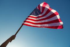 Stock Photo of American flag with stars and stripes hold with hands against blue sky